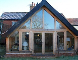 The creation of the large glazed gable frames the garden at Pinch Pot Cottage Norfolk and brings the outside in.